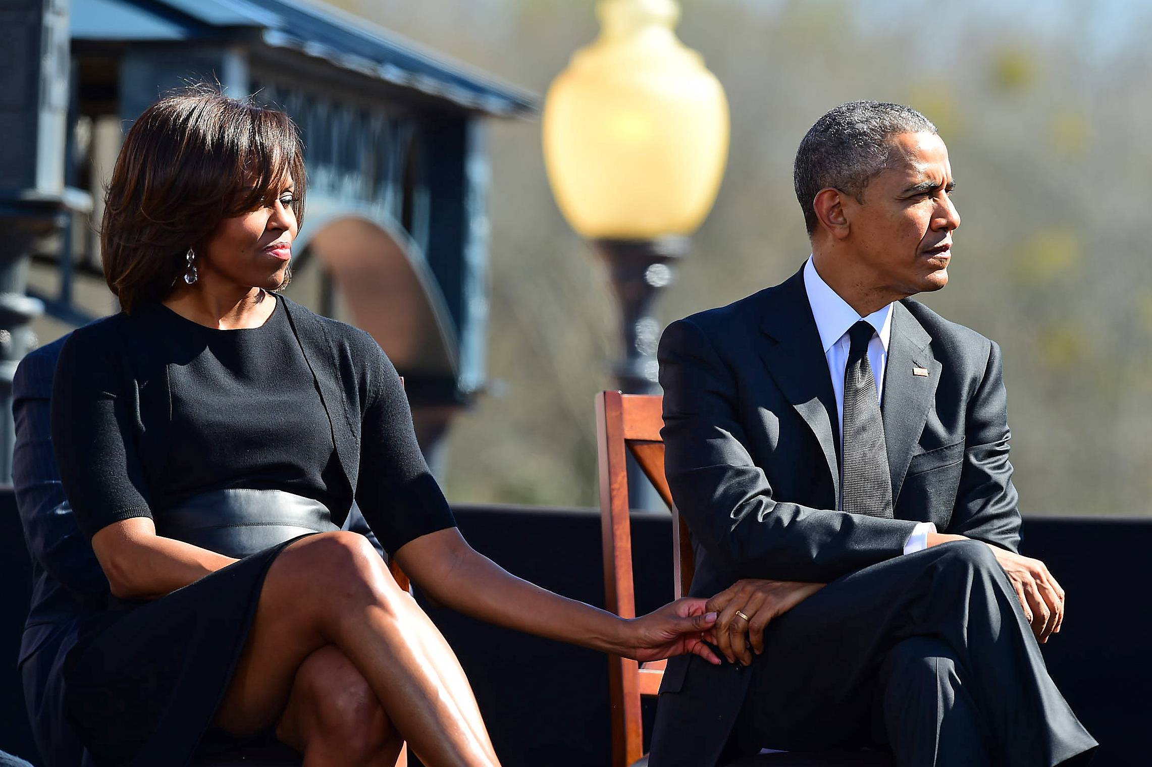 """First lady Michelle Obama holds the hand of her husband President Barack Obama as U.S. Rep. John Lewis, D-Ga., speaks before a symbolic walk across the Edmund Pettus Bridge, Saturday, March 7, 2015, in Selma, Ala. This weekend marks the 50th anniversary of """"Bloody Sunday,' a civil rights march in which protestors were beaten, trampled and tear-gassed by police at the Edmund Pettus Bridge, in Selma. (AP Photo/Bill Frakes)"""