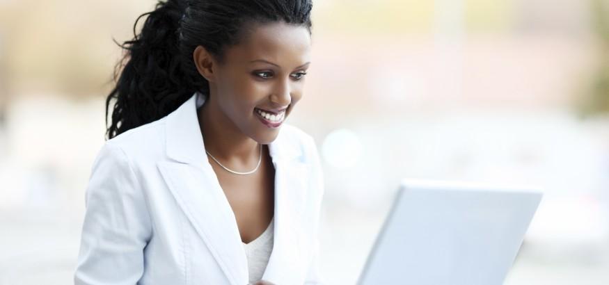 Beautiful African woman working on laptop.